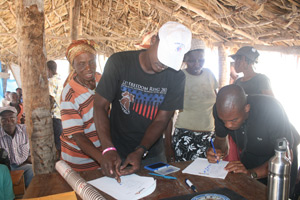 Pierre Theodore, Hope for Haiti assists member of the community of Platon sign their names and give their thumbprint to a contract stating that the people of Platon will assist in building the school.