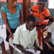Community Health Workers look over June reporting data