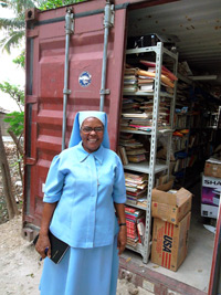 St. francois de sales's school director sr. gisele stands in front of a container donated by hope for haiti, which is now is used as a school library