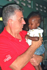 Vitamin Angels team member Paul with a malnourished child at Timoun Kontan Nutrition Clinic