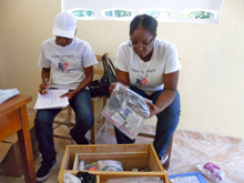Public Health nurses, Miss Claudine and Miss Pierrette, restock the first aid kit at the St. Laurent Secondary School