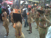 Dancers adorned in costume dance through the streets.