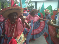 Dancers representing Comme Il Faut the Haitian cigarette company dance through the streets during the parade.