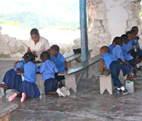 Preschool students work in a church that was severly damaged during the earthquake.