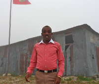 School Director stands in front of the cloud covered school.