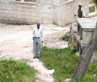 School Director stands waiting as Hope for Haiti truck approaches the rural school.
