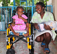 Bethsaida moise with her new wheelchair, as her mother looks happily on