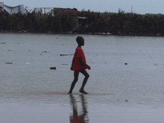 Child plays in the flooded low lying areas in aquin with houses in the distance