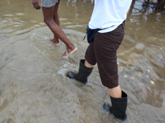Hope for Haiti staff members wade through flood waters to bring emergency relief.