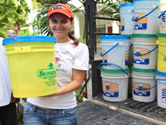 Program Manager, Jennifer Lang, unloads emergency buckets at Father Gousse's house