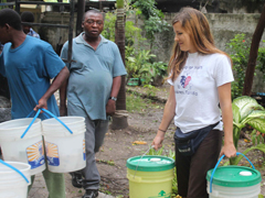 Program Manager, Paula Prince and program partner, Father Gousse, unload emergency buckets.