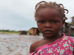 Young girl in Aquin outside of her flooded home.