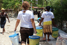 Program Assistant, Liz Warren, carries emergency buckets to Cote de Fer residents after Tropical Storm Isaac.