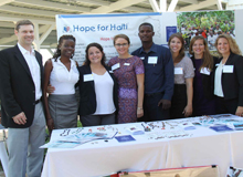 The Hope for Haiti team poses by the table with new Board Member, Kevin Ashley