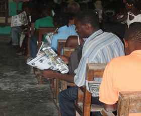Morency community members read about cholera prevention.