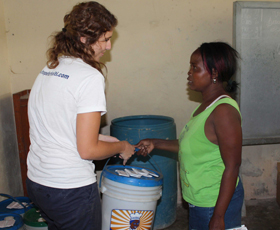 Program Assistant Liz Warren distributes emergency buckets and ORS to a community member