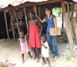 Hope for Haiti staff member, Paula Prince, with Micheline in front of her damaged home.
