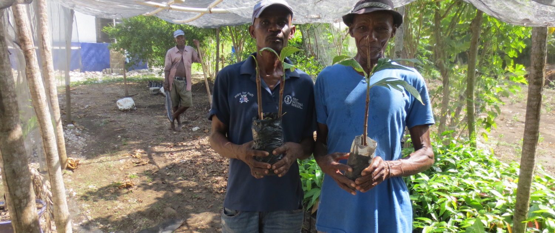 Two Farmers Hold Seedlings in the School Garden